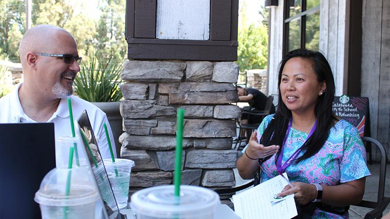 Dr. Adam Aréchiga talks with alumna Tori Dang in Riverside