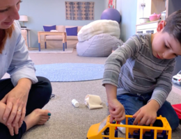 Child plays with bus and gauze as play therapist observes