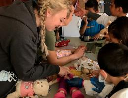 A Child Life Specialist graduate student helps run a teddy bear clinic.