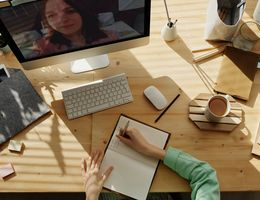 individual makes notes at a desk while in a videoconference