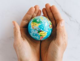 person holds model of the world in their hands