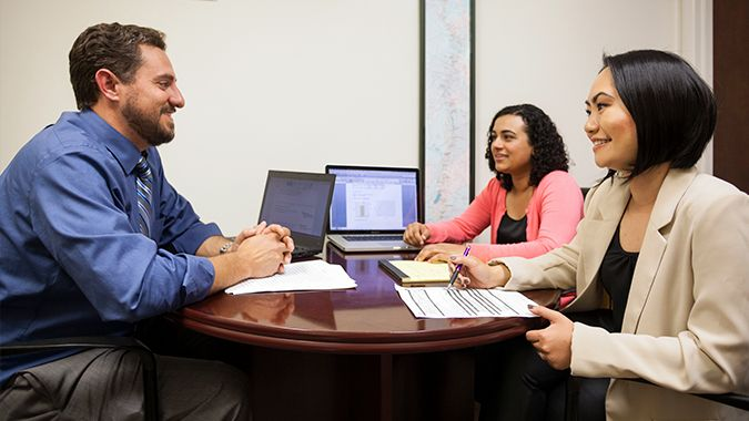 faculty member talking with two female students at his desk